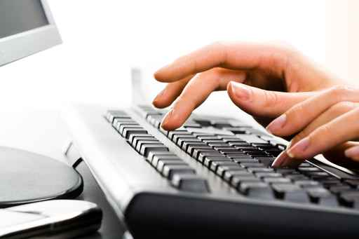 A business lady's hands on the keys typing documents